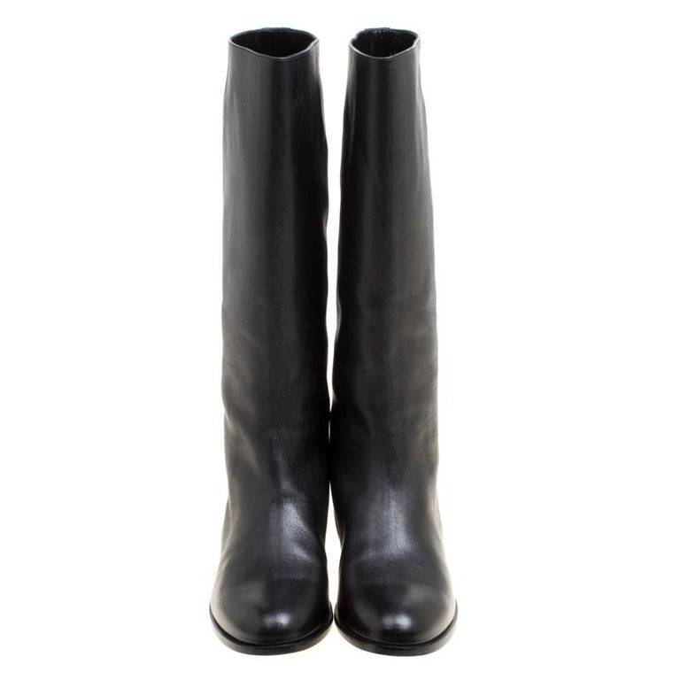 Stay on style with this pair of boots from Alexander McQueen! Beautifully crafted from leather, these mid-calf boots carry round toes and trim of spikes on the back. Waltz around town in this lovely pair!  Includes: Original Box