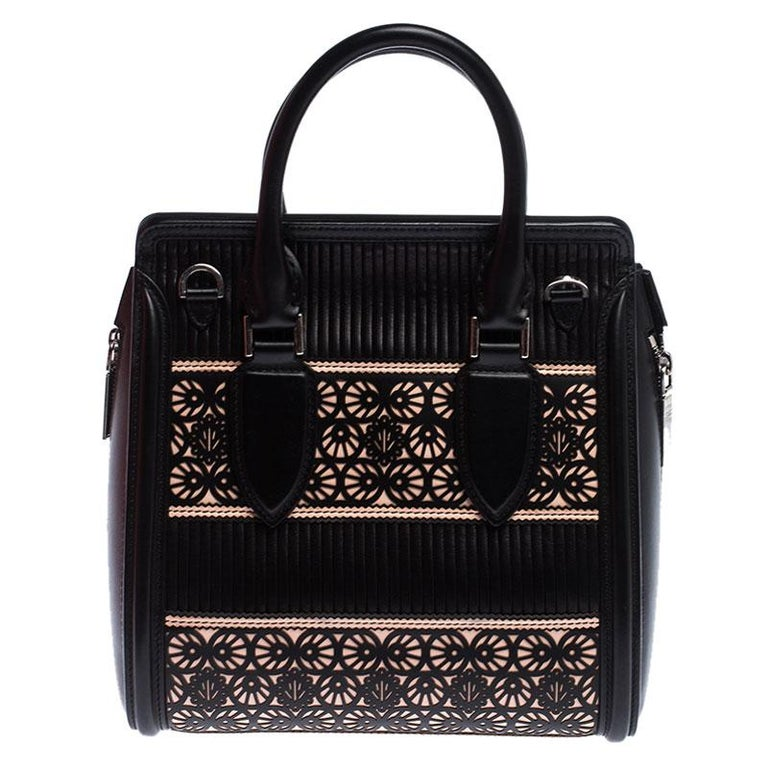 Every woman needs a bag that is pretty and functional, just like this one from Alexander McQueen. Crafted from leather, it has been styled with laser cuts and a flap leading to a spacious suede interior. Held by two top handles, this is definitely