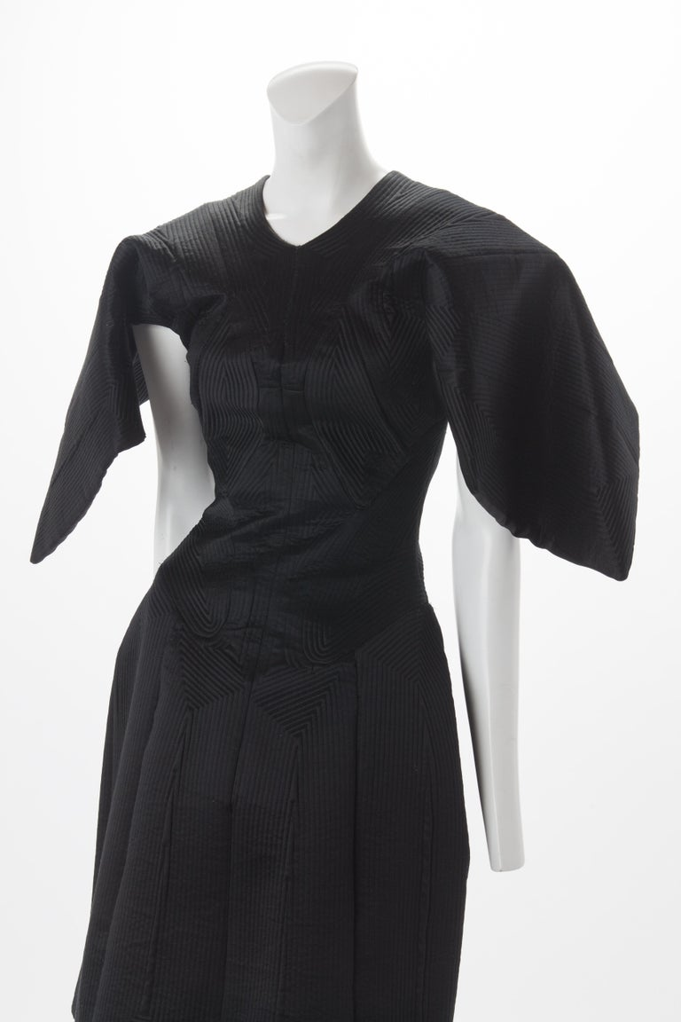 Alexander McQueen Black Quilted Satin Cocktail Dress with Batwing Sleeves, 2009. Quilted structured dress with seaming creating geometric pattern throughout. Batwing mid-length sleeves that create a cape-like look from the back of this dress. Hidden
