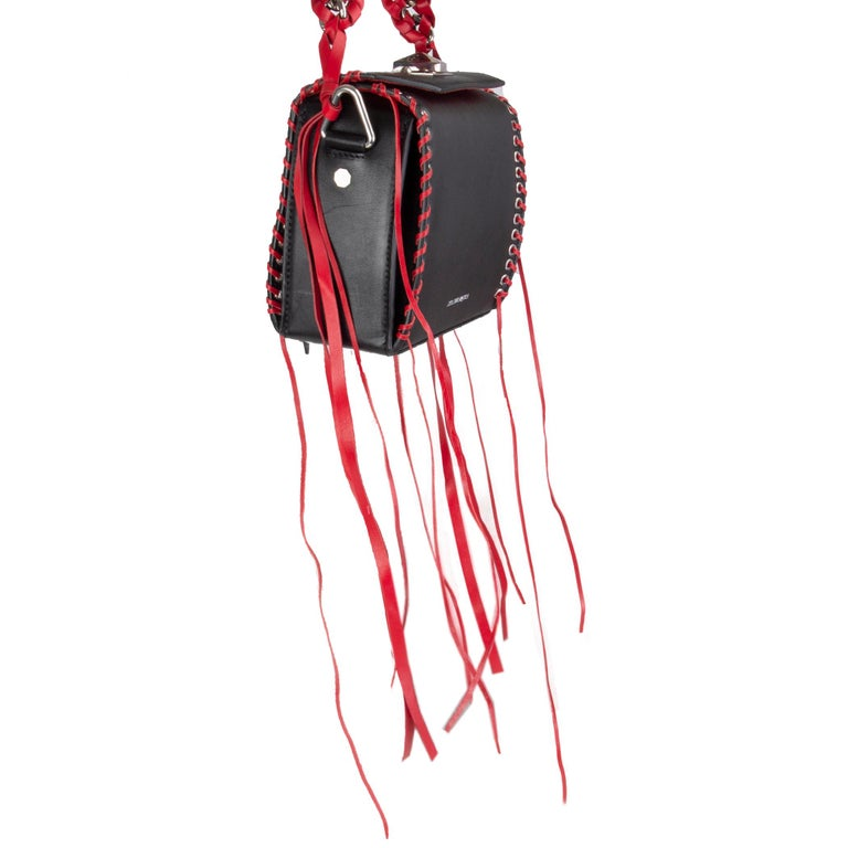 Alexander McQueen 'Box 19' shoulder bag in black leather with silver-tone eyelits and read leather whipstitch details and red leather and chain handle. Detachable shoulder strap. Opens with a turn-lock on top. Inside is divided into three