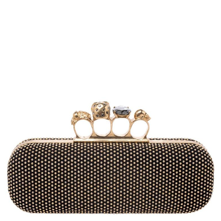 This Box Clutch from Alexander McQueen exudes versatility and luxury. Crafted from gold-tone studded black suede it has a sleek finish and comes with a well-sized interior. This piece is complete with the brand's iconic skull-knuckle fastening.