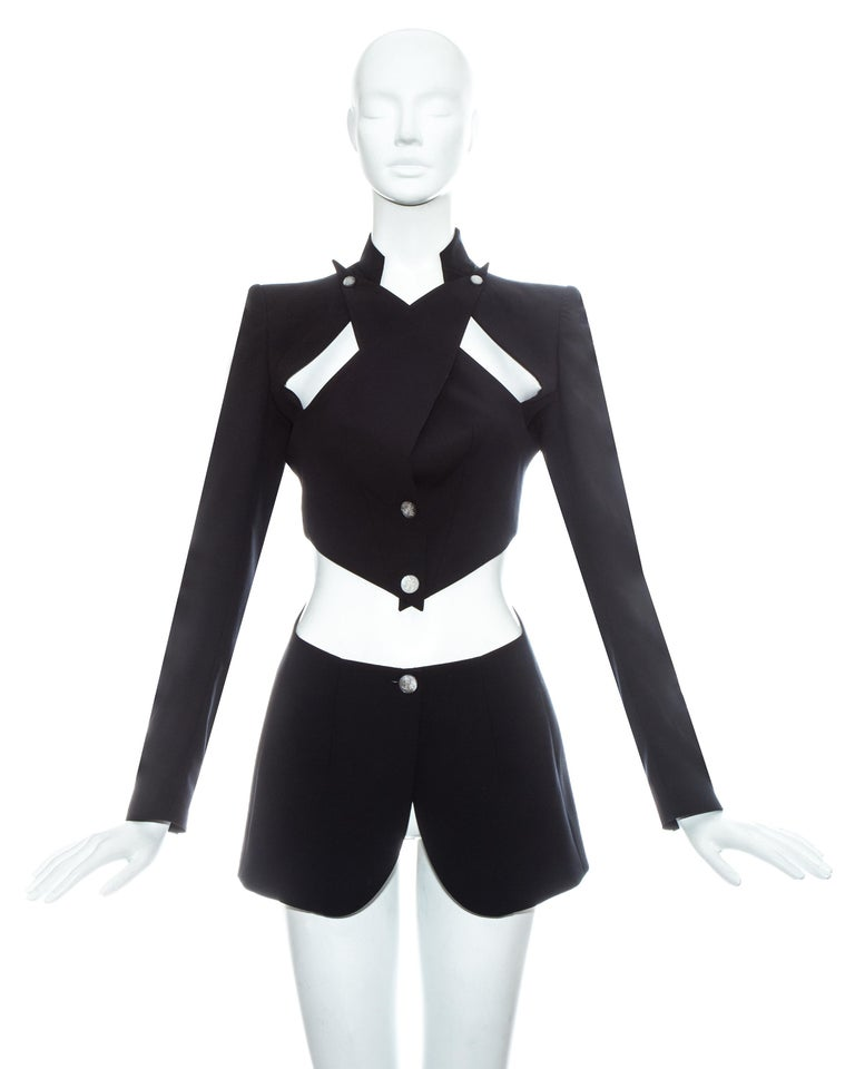 Alexander McQueen; black wool blazer jacket. Exaggerated lapels cross over and fasten on the shoulder line and cut out on the midriff.     Spring-Summer 1999