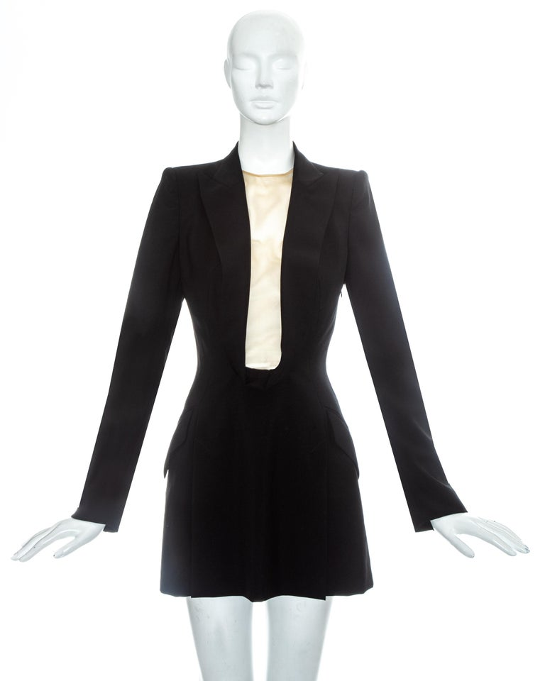 Alexander McQueen black wool blazer mini dress with shawl lapel, deep cleavage with nude mesh and front vent on skirt.  Golden Shower, Spring-Summer 1998