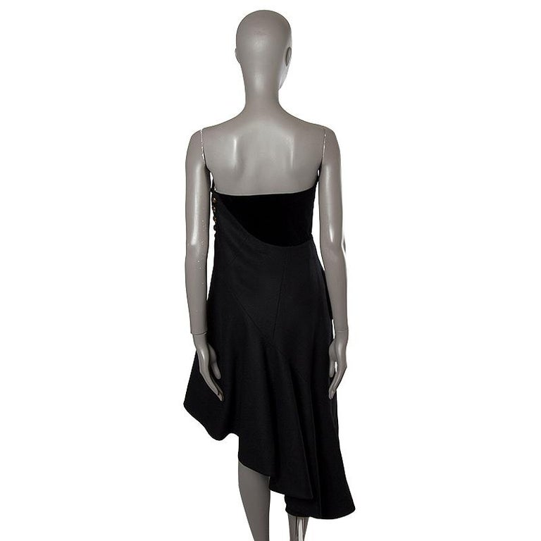 Alexander McQueen Pre-FW'11 strapless dress in black virgin wool (90%), cotton (7%), and silk (3%). With integrated boned bustier and asymmetric hemline. Closes wirh inside zipper, hidden snap, and golden bottons on the side. Lined in cream satin