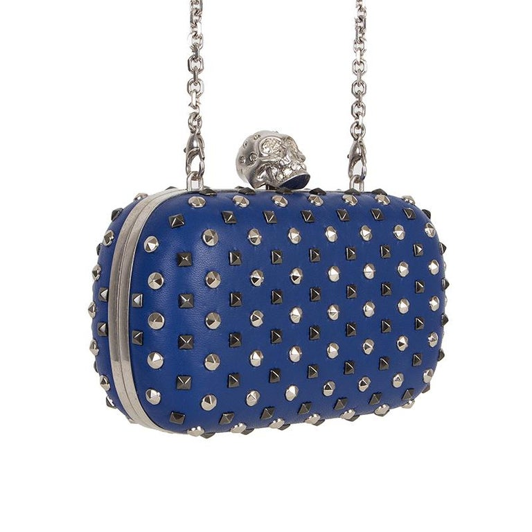 Alexander McQueen frame studded crystall-skull clutch in indigo leather and silver-tone studds with skull in silver-tone metal and crystals. Opens with clip-lock on top. Lined in blue leather. Comes with detachable shoulder strap. Has been carried