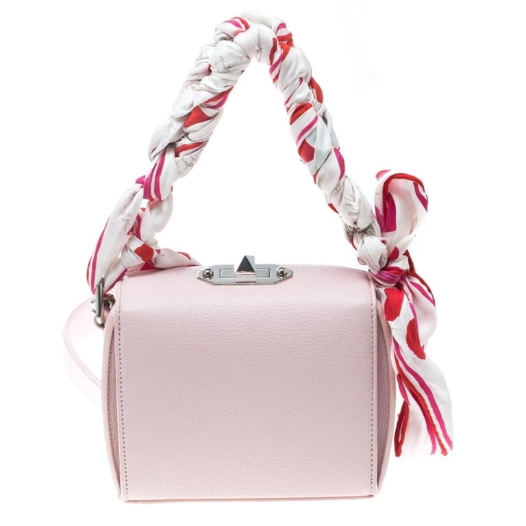 From the house of Alexander McQueen comes this gorgeous box shoulder bag that will perfectly complement all your outfits. It has been luxuriously crafted from blushed pink leather and styled into a box shape with a silver-tone turn lock on top and a