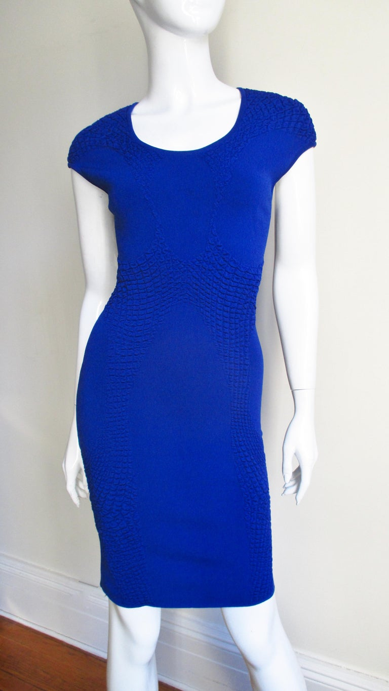 A bright blue knit bodycon dress from Alexander McQueen. It has a crew neckline and cap sleeves. There are no closures, it slips on over the head. Fits sizes Extra Small, Small, Medium.  Bust 32-36