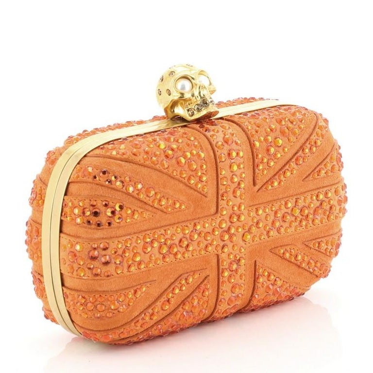 This Alexander McQueen Britannia Skull Box Clutch Studded Suede Small, crafted with orange studded suede, features Union Jack flag inspired crystal studs design, hinged metal frame, and gold-tone hardware. Its skull clasp closure opens to an orange