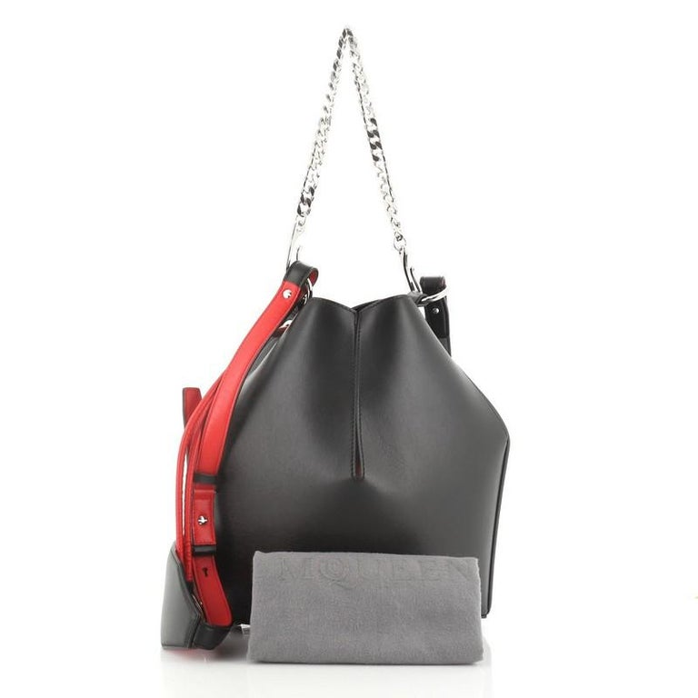 This Alexander McQueen Bucket Bag Leather Medium, crafted in black and red leather, features a chain-link handle, leather shoulder strap. Its cinch closure opens to a black microfiber interior.  Estimated Retail Price: $2,490 Condition: Great. Minor
