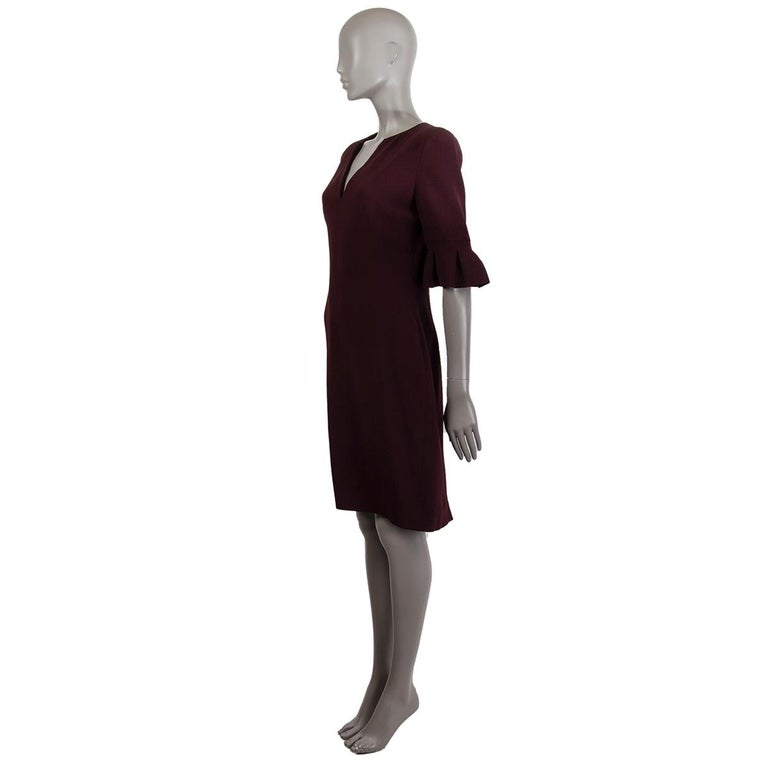 Alexander McQueen short-sleeve knee-length sheath v-neck dress in burgundy acetate (50%) and rayon (50%). Lined in acetate (74%) and silk (26%). Dress features padded shoulders and pleaded detail at sleeve. Opens with a zipper on the back. Has been