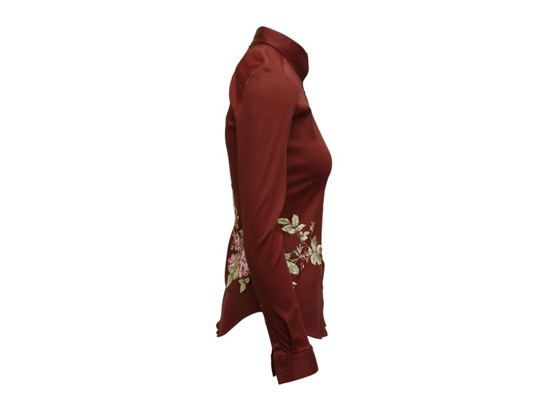 Product details:  Burgundy floral embroidered blouse by Alexander McQueen.  From the Fall 1997 collection.  Asymmetrical point collar.  Long sleeves.  Single button cuffs.  Button-front closure.  Shirttail hem.  32