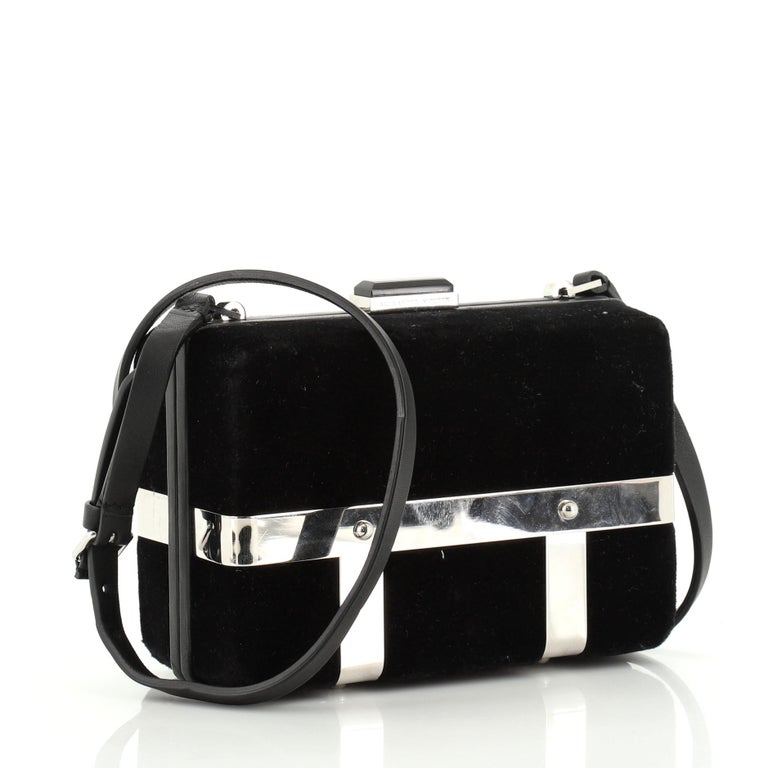 This Alexander McQueen Caged Box Bag Velvet, crafted from black velvet, features a flat leather shoulder strap, rectangular silhouette encased in a cage, and sliver-tone hardware. It opens to a black suede interior.   Estimated Retail Price: