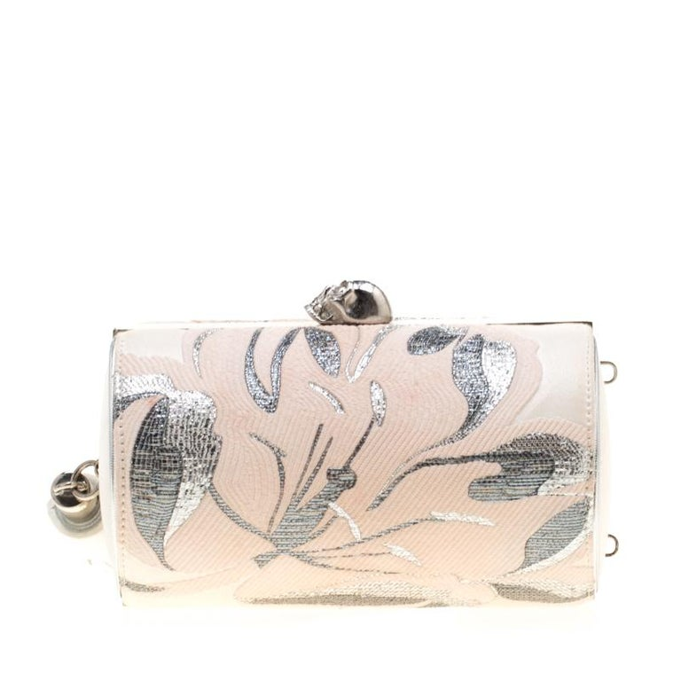 This clutch by Alexander McQueen is one you will love carrying around. It is subtle, captivating, and stylish. The clutch is made from cream satin and covered in soothing florals. The signature skull on top opens to a leather interior and to