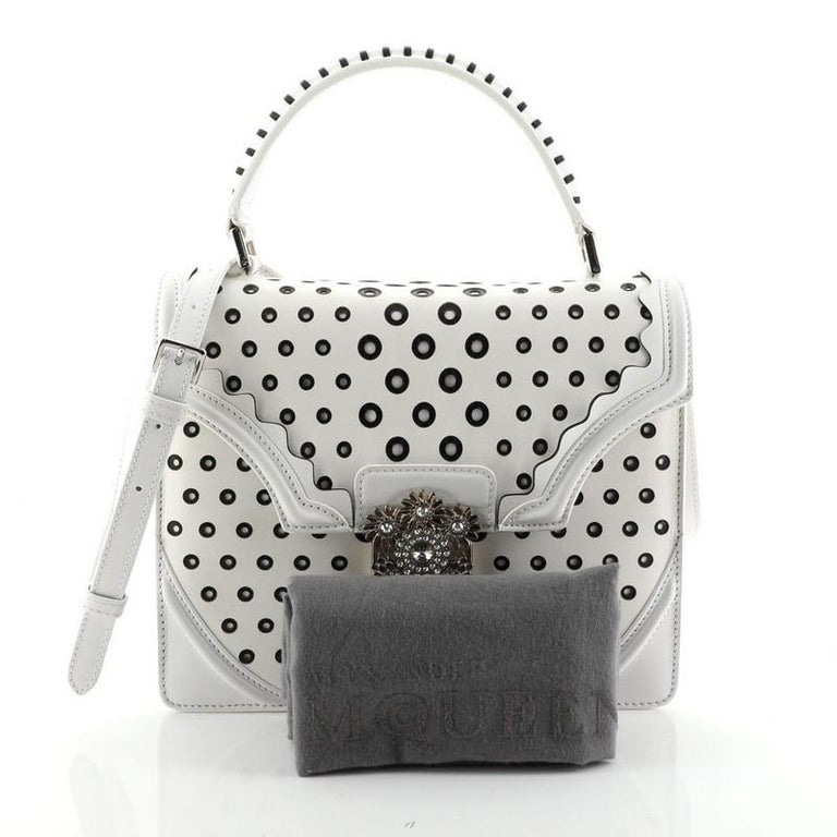 This Alexander McQueen Flower Satchel Perforated Leather Medium, crafted in white leather, features a leather top handle, perforated detailing and silver-tone hardware. Its push-lock closure opens to a black suede interior with a center zip