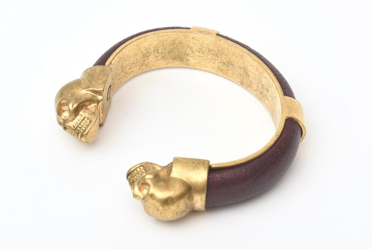 This fabulous and iconic Alexander McQueen gold plated and aubergine brown pebbled leather bracelet can be worn two ways. it acts as a bangle or a small cuff bracelet and of course can be paired with other bracelets in gold to create a sculptural