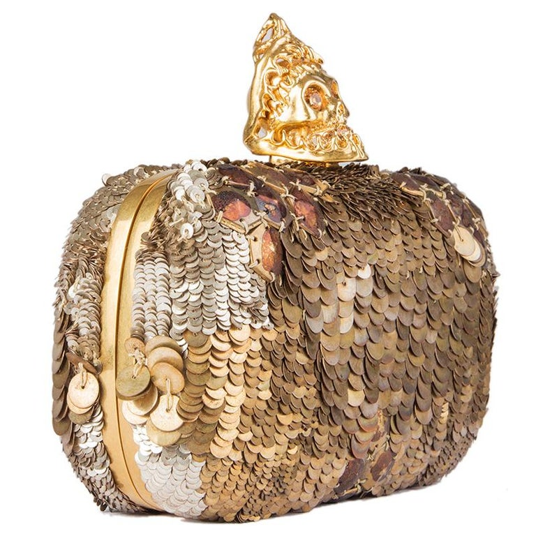 Alexander McQueen skull box clutch embellished with gold and silver-tone sequins. Opens with a crystal embellished gold-tone metal skull and is lined in dark brown leather. Has been worn and some sequins on top are missing. Overall condition is very