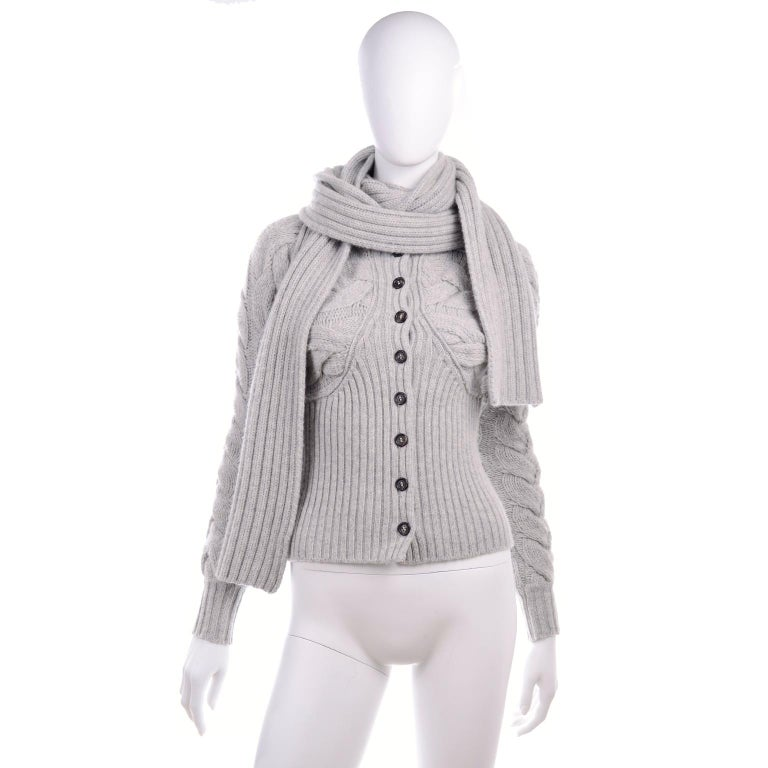 This is a wonderful gray wool cable knit button front cardigan sweater from Alexander McQueen.  We love designer pieces like this because they appear simple at first but then have that special element that makes them wonderfully unique. The sweater
