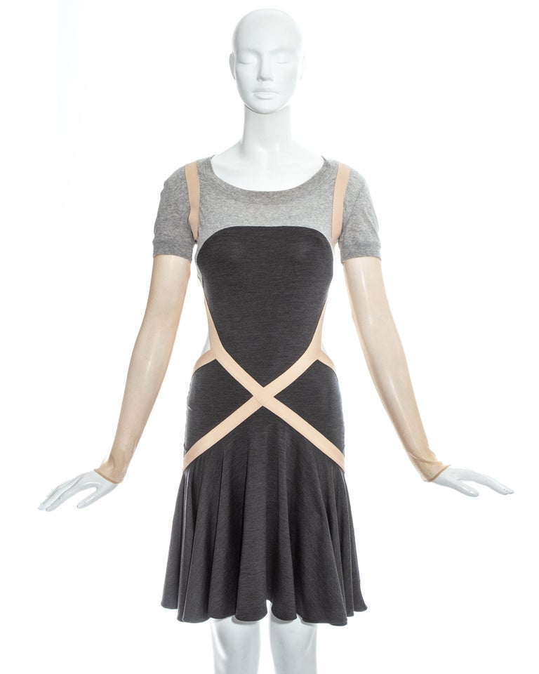 Alexander McQueen grey jersey dress with nude mesh sleeves, elastic bandage construction and flounce skirt.   Spring-Summer 2004
