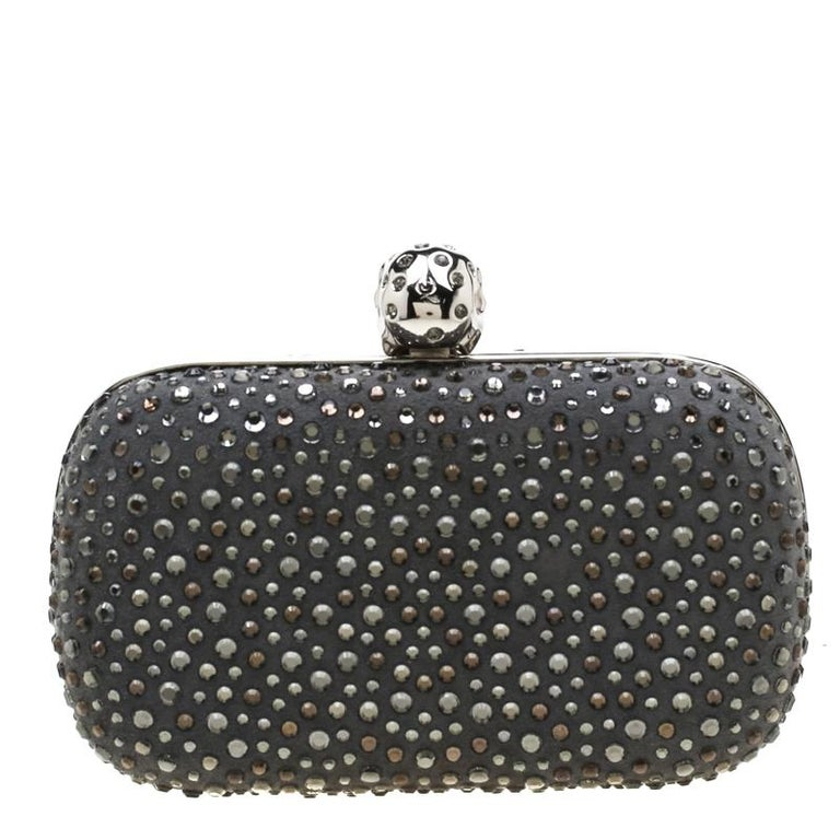 How utterly breathtaking is this clutch by Alexander McQueen! It is luxurious, well-crafted and overflowing with style. It has a grey nubuck leather exterior with gorgeous crystal embellishments and a skull lock on top. This creation will lift all