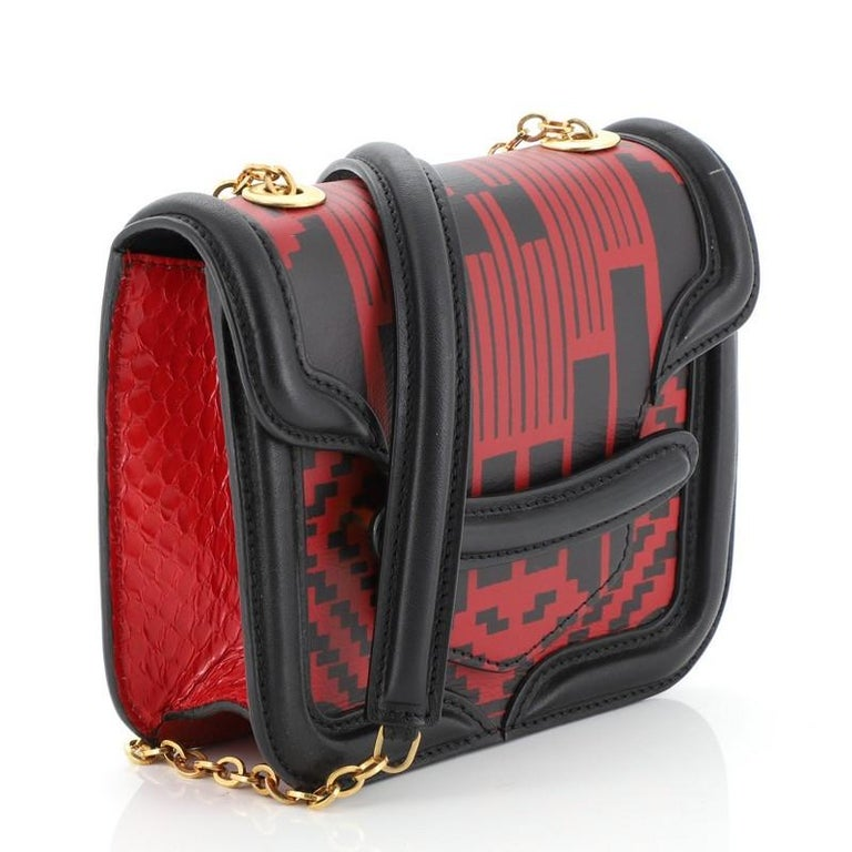 This Alexander McQueen Heroine Satchel Printed Leather with Python Mini, crafted from black and red printed leather with genuine red python, features chain link strap with leather pad and gold-tone hardware. Its flap opens to a black microfiber