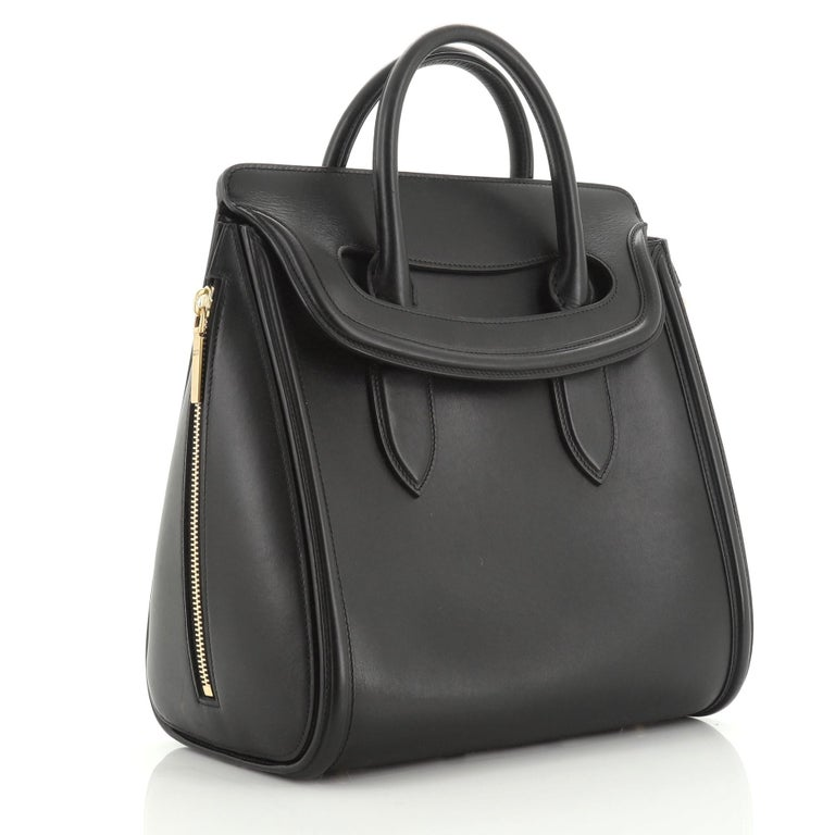 This Alexander McQueen Heroine Tote Leather Large, crafted from black leather, features dual rolled leather handles, gusseted side zipper details, protective base studs, and aged gold-tone hardware. Its flap closure opens to a gray suede interior