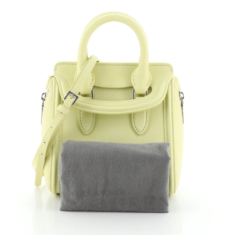 This Alexander McQueen Heroine Tote Leather Mini, crafted in yellow leather, features dual rolled leather handles, oversized side zipper details, embossed logo at the center, and silver-tone hardware. Its flap closure opens to a gray suede interior