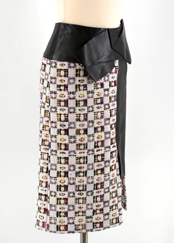 Alexander McQueen Leather-Trimmed Tweed Skirt  Alexander McQueen tweed skirt with pleated leather trim. Natural waist. Slim A-line silhouette. Straight hem with front slit. Hidden back