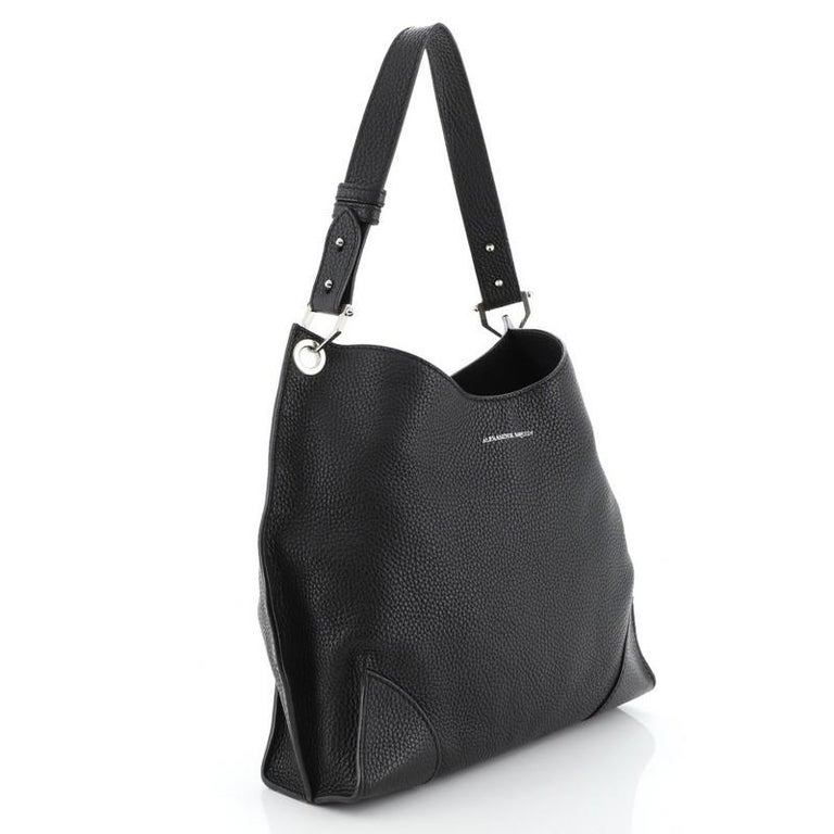 This Alexander McQueen Legend Hobo Leather Medium, crafted in black leather, features a looping leather handle and silver-tone hardware. Its magnetic closure opens to a neutral fabric interior showcases a neutral fabric interior with zip pocket.