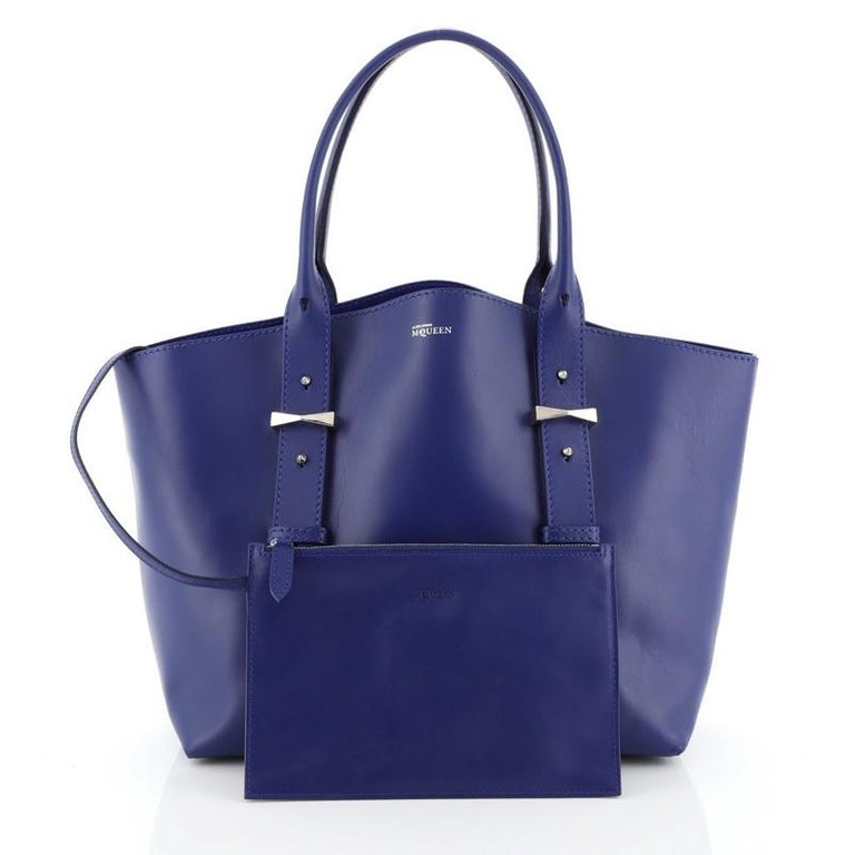 This Alexander McQueen Legend Tote Leather Medium, crafted in blue leather, features dual-rolled leather handles with belted leather details, protective base studs and silver-tone hardware. Its wide top opening showcases a blue suede and leather