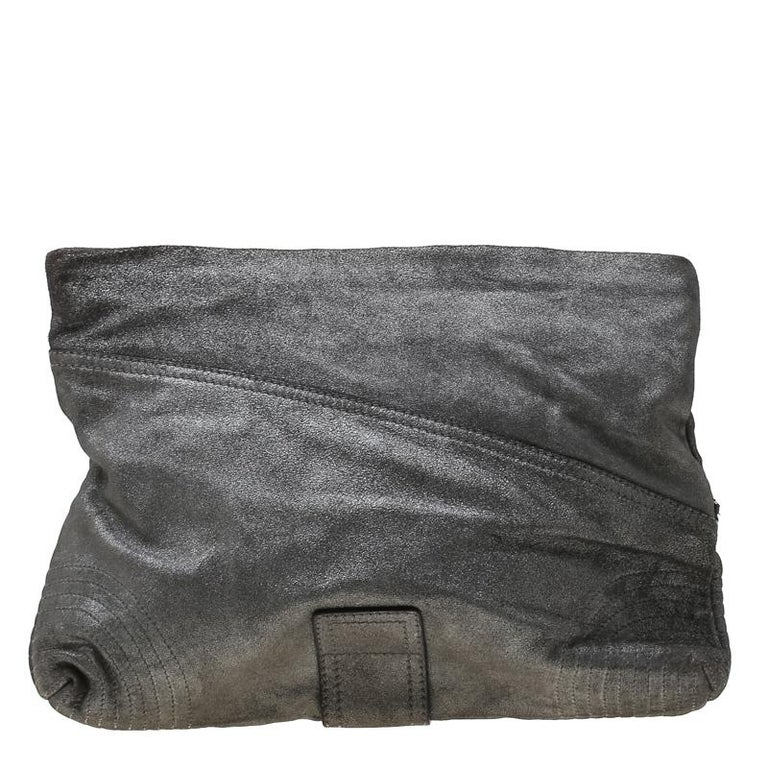 Made of textured leather, this metallic grey clutch from Alexander McQueen is a creation worthy of being yours. It is designed with zip details, a fabric interior, and a wristlet. The clutch is well-made and functional.  Includes: The Luxury Closet