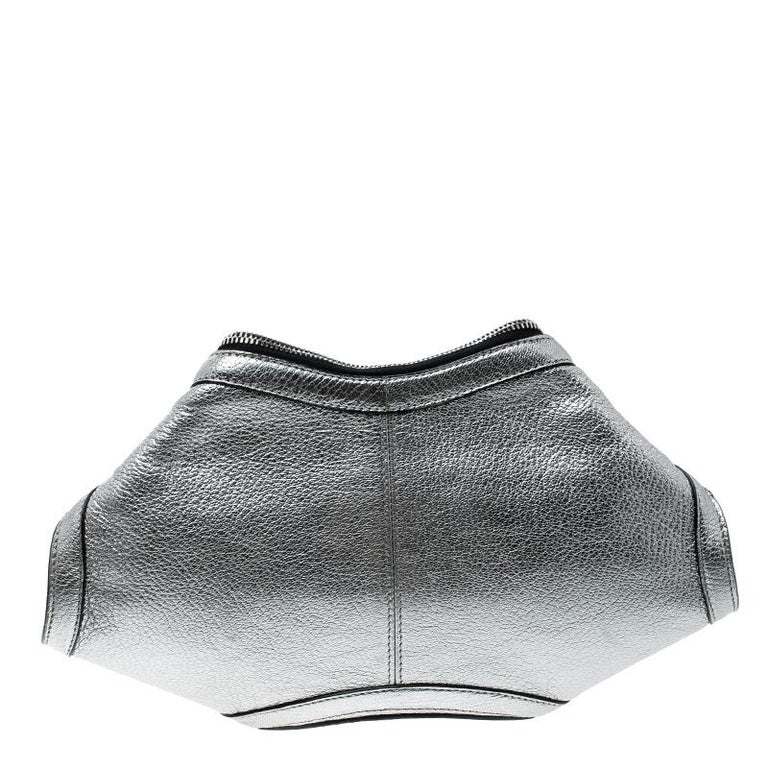 Bring out your edgy side with this De Manta Clutch from Alexander McQueen. It flaunts a unique silhouette and is crafted from silver leather. The clutch has a metallic finish, folded top corners and double zippers that lead to a spacious fabric
