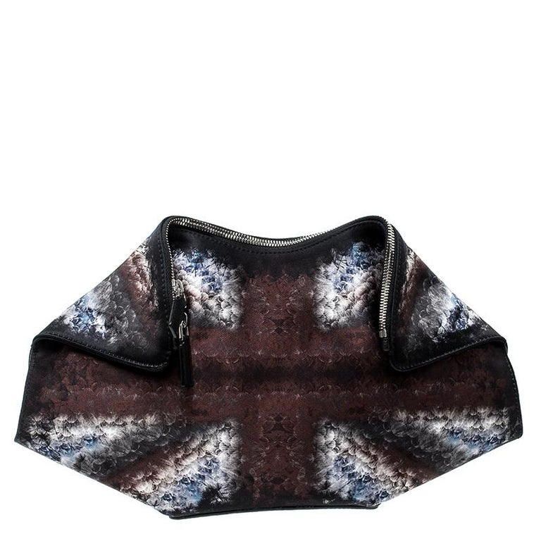 Alexander McQueen brings you this super-edgy clutch that carries a silhouette which will surely grab the attention of your onlookers. It has prints all over the satin covering, folded top edges and double zippers that lead to a fabric