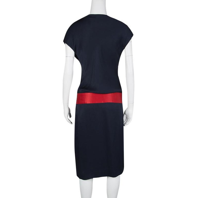 This is a dress that simply screams glamour and festivity in all of its design. The fitted body is crafted out of pure silk in a gorgeous navy blue and is accented by a bold red belt detailing at the drop waist. The knot detail at the neck adds to