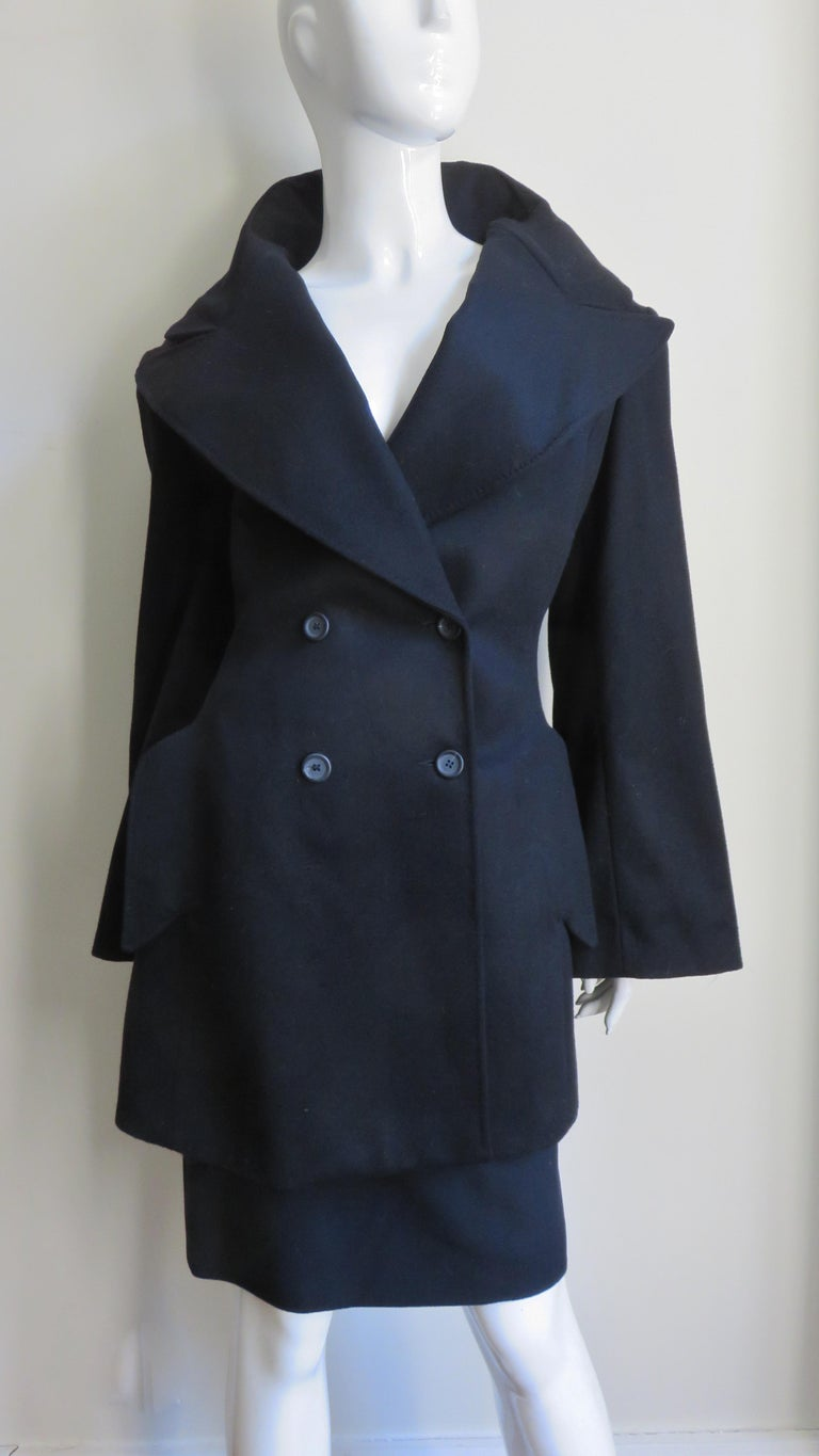 A fabulous black cashmere skirt and jacket with a dramatic stand up collar from Alexander McQueen.  The double breasted jacket has a stand up back lapel collar which frames the face fabulously, vertical hip flap pockets and full long sleeves. The