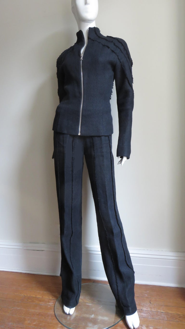 An incredible black linen jacket and pant set from Alexander McQueen.  The jacket has a stand up collar, long sleeves and multiple seamed, pieced panels along the shoulders, sleeves and in flattering angles in the back.  It is fitted at the waist