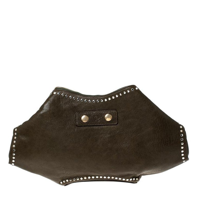 Alexander McQueen brings you this super-edgy clutch that carries a silhouette which will surely grab the attention of your onlookers. It has an olive green shade, folded top edges and double zippers that lead to a fabric interior.  Includes: The