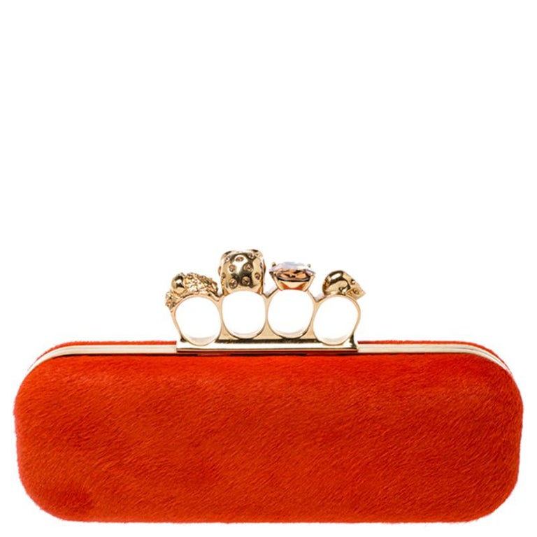 This Box Clutch from Alexander McQueen exudes versatility and luxury. Crafted from calf hair, it has a grand finish and comes with a leather interior. This piece is complete with the brand's iconic skull-knuckle slot on top. Flaunt this orange