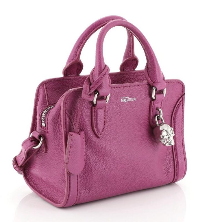This Alexander McQueen Padlock Zip Around Tote Leather Mini, crafted from purple leather, features dual rolled handles and silver-tone hardware. Its zip closure opens to a black fabric interior with side zip and slip pockets.   Estimated Retail