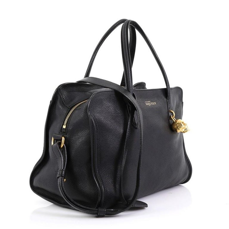 This Alexander McQueen Padlock Zip Around Tote Leather Small, crafted from black leather, features dual rolled handles, signature skull padlock, and gold-tone hardware. Its zip-around closure opens to a black fabric interior with zip and slip