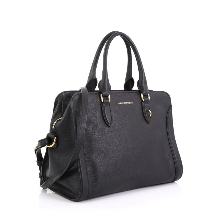 This Alexander McQueen Padlock Zip Around Tote Leather Small, crafted from black leather, features dual rolled handles and gold-tone hardware. Its zip-around closure opens to a black fabric interior with zip and slip pockets.   Estimated Retail