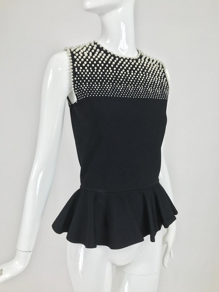 Alexander McQueen pearl bodice sleeveless peplum top in black stretch fabric. Jewel neckline closes at the back with a loop and button. The upper bodice front and back is covered with small, medium and large faux pearls. The top is fitted and