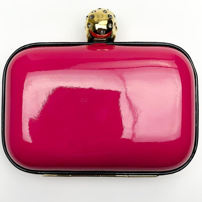 This minaudière is signed by Maison Alexander McQueen. It is a bright pink and it is surmounted on the clasp of a vanity, an allegorical representation of death. The minaudière is in very good condition. Presence of the brand on the interior velvet,