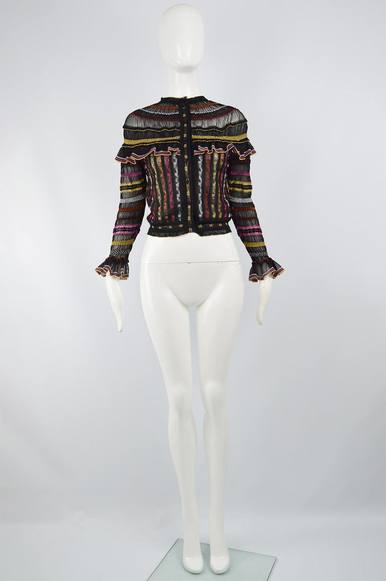 A stunning vintage women's cardigan / jacket by Alexander McQueen from the Pre Fall 2018 collection. In a semi sheer black knit with a ruffled trim and an incredible multicolored metallic lame woven throughout.  Size: Unlabelled; fits like a women's