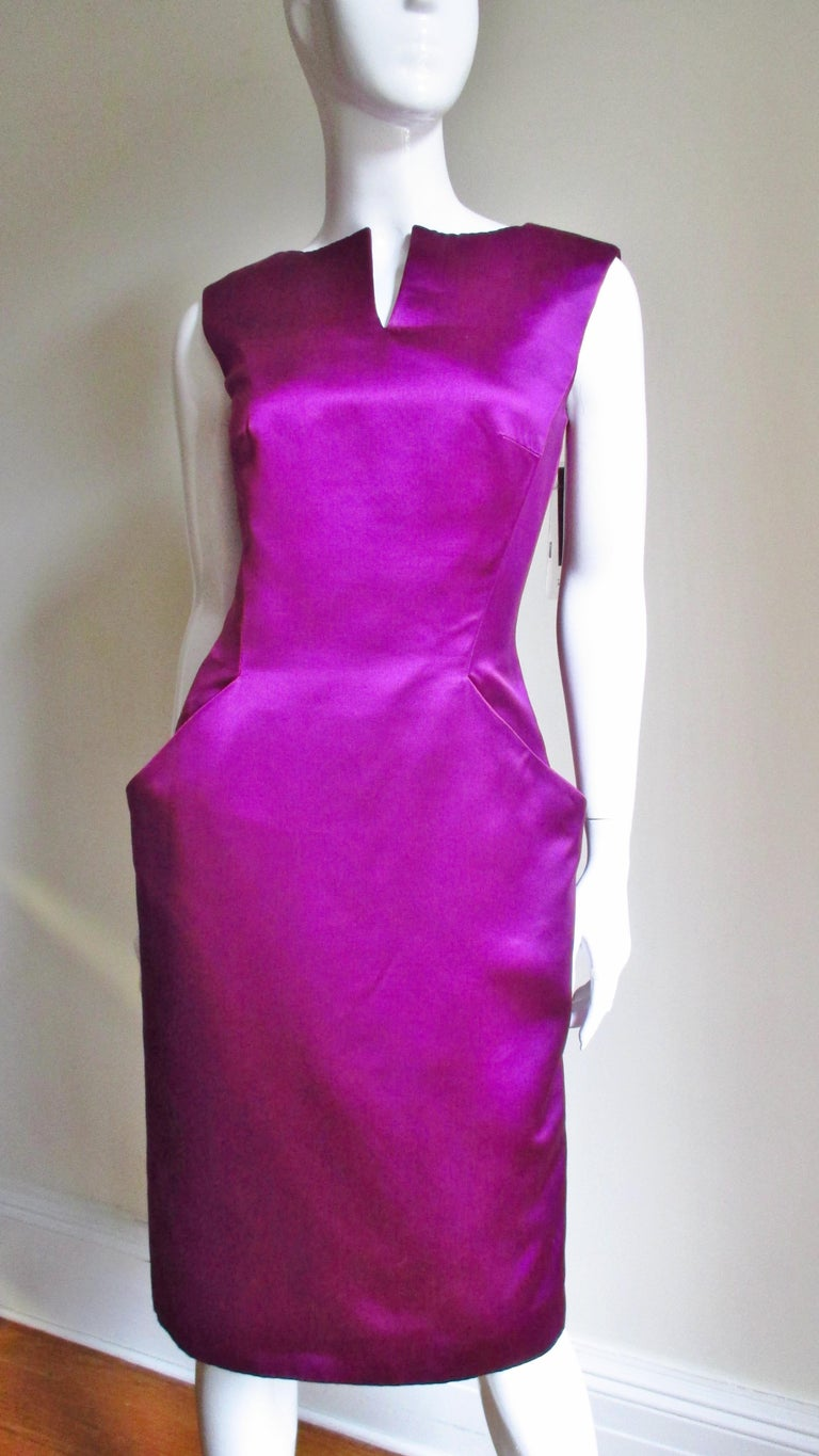 A fabulous fuchsia silk dress from Alexander McQueen.  It is sleeveless with a slit at the neckline. The center front bodice is in one piece extending down into angled pockets creating clean geometric lines. The back is V cut to the waist, has back