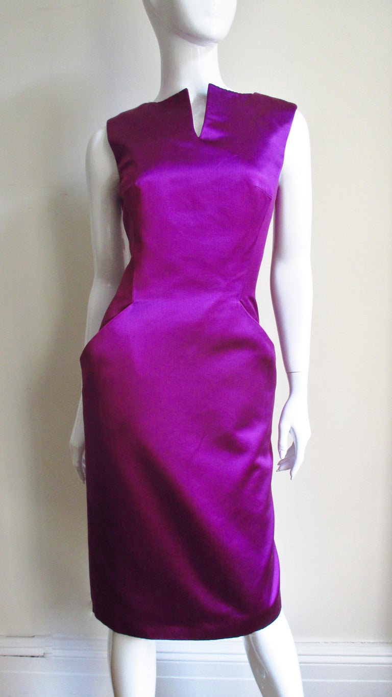 A fabulous fuchsia silk dress from Alexander McQueen.  It is sleeveless with a slit at the center front neckline and hip pockets. The back has a deep V cut to the waist and the skirt has a kick pleat at the center back hem.  The dress has a back