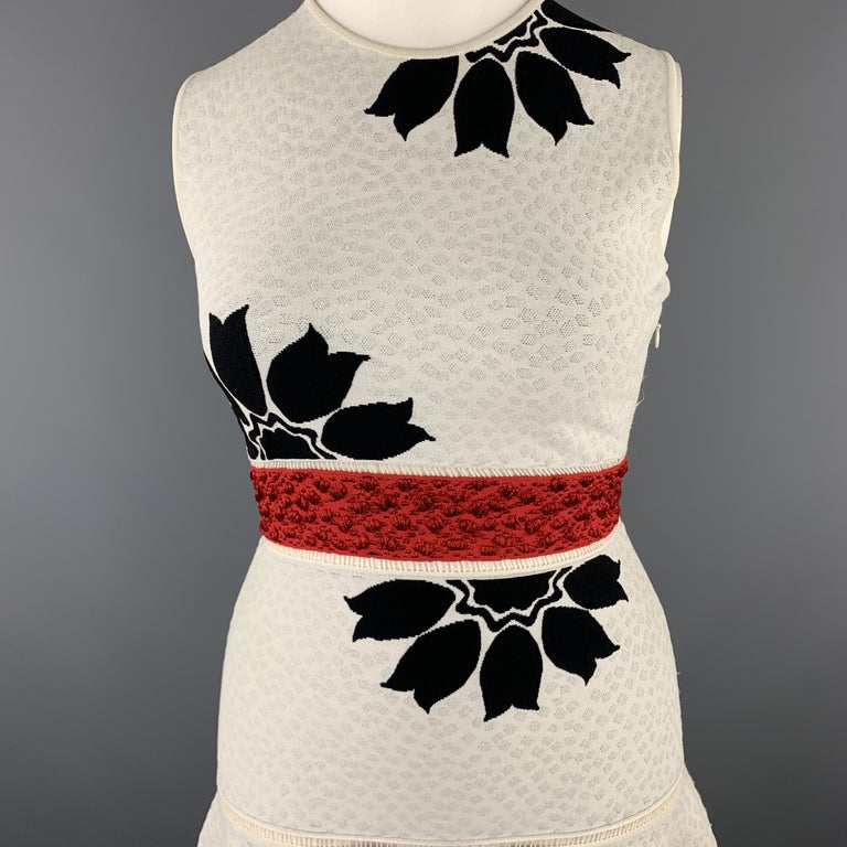 ALEXANDER MCQUEEN cocktail dress comes in off white textured stretch knit with a black floral pattern throughout, red belt panel, fit to flair ruffled skirt, and cutout trim. Made in Italy.  Excellent Pre-Owned Condition. Marked: