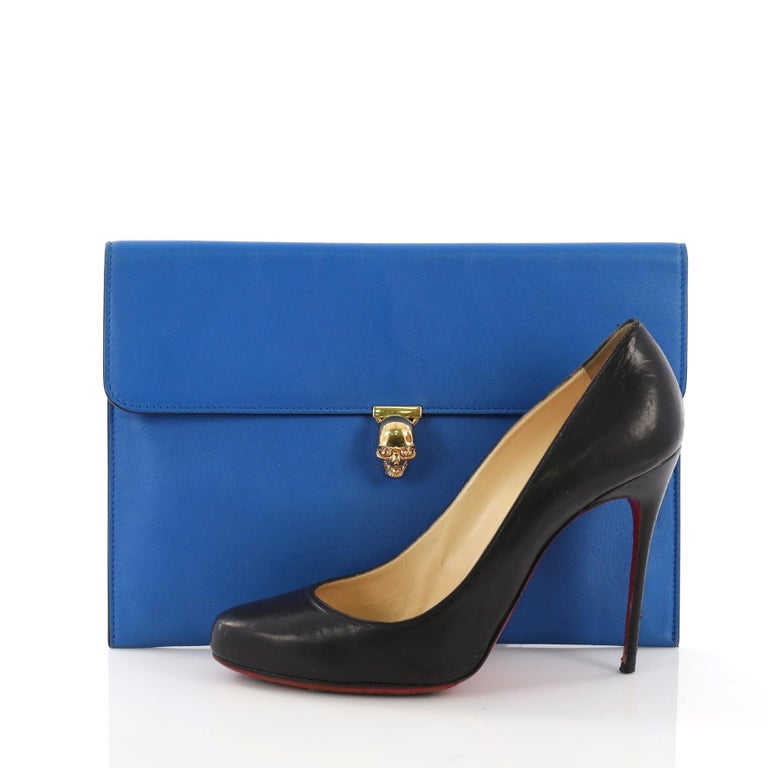 This Alexander McQueen Skull Envelope Clutch Leather, crafted from blue leather, features flap top with signature skull clasp and gold-tone hardware. Its clasp closure opens to a blue leather interior. **Note: Shoe photographed is used as a sizing