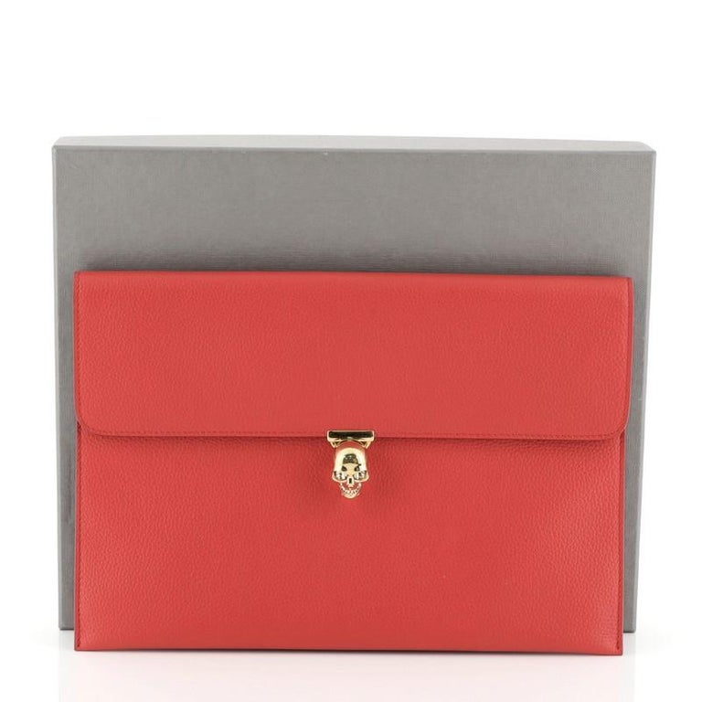This Alexander McQueen Skull Envelope Clutch Leather, crafted from red leather, features flap top with signature skull clasp and gold-tone hardware. Its clasp closure opens to a black leather interior.   Estimated Retail Price: $745 Condition: