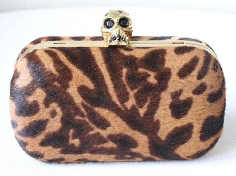 The combination of opulent ocelot print and a Swarovski crystal-encrusted skull makes Alexander McQueen's compact box clutch a darkly decadent accessory. Ocelot-print calf hair. Detachable buckle-fastening shoulder strap. Gold brass frame. Fully