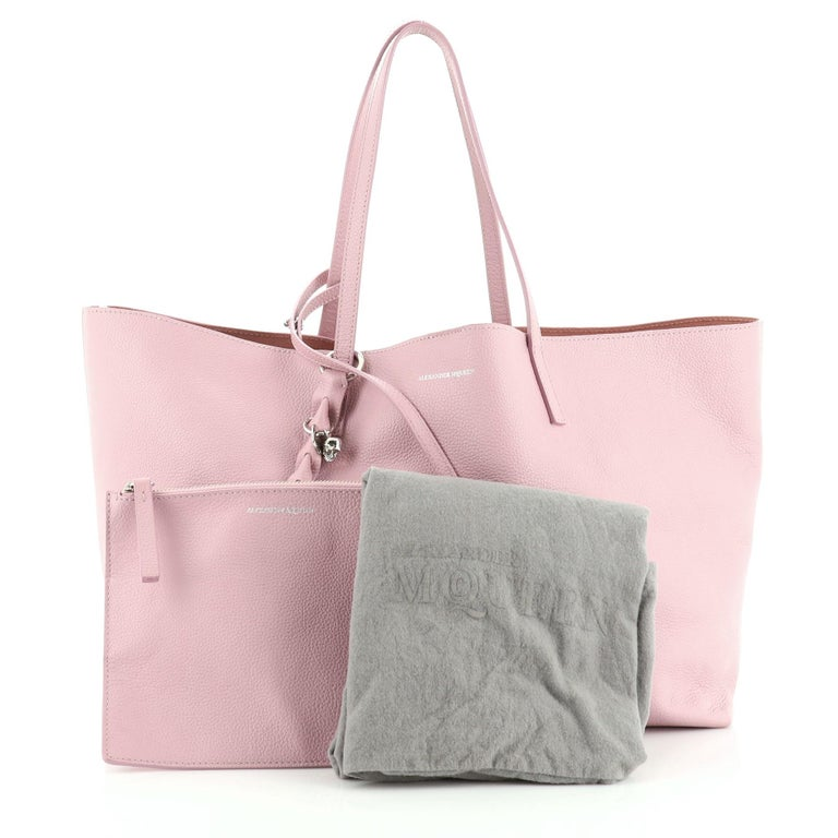 This Alexander McQueen Skull Open Shopper Tote Leather Large, crafted in pink leather, features dual flat leather handles, signature silver skull padlock, and silver-tone hardware. Its wide-open top opens to a pink suede interior.   Estimated Retail